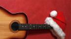 Eine Gitarre und eine Samichlaus-Mütze.