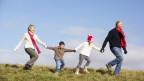 Grosseltern wandern mit Enkelkindern über grüne Wiese.