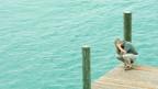 Mann am See gebückt und verzweifelt