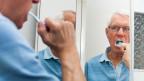 Senior putzt sich die Zähne.