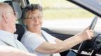 Eine Senior fährt mit dem Auto.
