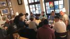 Alte und junge Menschen diskutieren am Tisch.