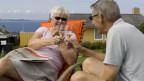 Mann und Frau im reiferen Alter auf Liegestuhl stossen mit Prosecco an.