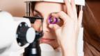 Auge einer Frau wird vom Augenarzt mit Geräten untersucht