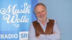 Peter Reber steht vor dem SRF Musikwelle Logo.