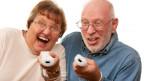 Zwei Senioren spielen mit Konsole.
