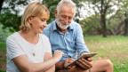 Ein Senioren-Paar sitzt draussen und spielt mit dem Tablet.
