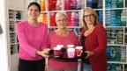 Drei Frauen halten ein Tablar mit Cupholders in der Hand.