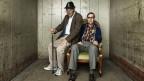 Zwei Schauspieler verkörpern Senioren. Sie sitzen auf einem Plsterstuhl.