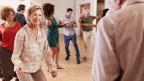Eine lachende Seniorin beim Tanzen.