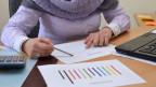 Eine Frau sitzt am Bürotisch und studiert ein Diagramm.