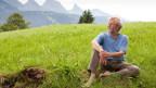 Peter Roth sitzt barfuss auf einer grünen Wiese.