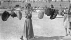 Eine junge Winzerin trägt an einer Stange Körbe.