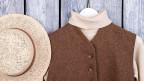 Ein Strohhut, ein Pullover und eine Weste.