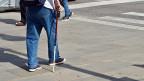 Ein Mann mit Spazierstock auf einer Strasse.