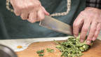 Koch schneidet Wirsing auf einem Holzbrett.