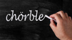 Ein Mann schreibt mit Kreide das Wort «chörble» auf eine Wandtafel.