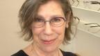 Eine lachende Frau mit Brille.