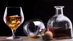 Cognacgläser halb gefüllt neben Flasche Alkohol.