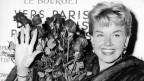 Doris Day hält einen Rosenstrauss in der Hand und winkt.
