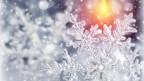 Ein Schneestern mit einem Kerzenlicht im Hintergrund.