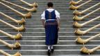 Eine Frau in Tracht läuft eine Treppe zwischen Alphörnern hoch.