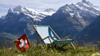 Ein Liegestuhl und eine Schweizer Flagge stehen auf einer Wiese mit Berge im Hintergrund.