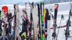Viele Skis stehen bei einem Skiständer.