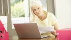 Seniorin sitt nachdenklich hinter Laptop.