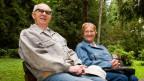 Ein Seniorenpaar sitzt auf einer Bank in der Natur.