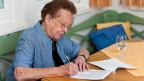 Eine ältere Frau sitzt am Tisch und schreibt ihren Nachlass.