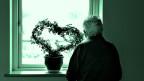 Ein alter Mensch steht vor einem Fenster.