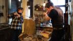 Eine Frau und ein Mann stehen in der Werkstatt und giessen Zinn.