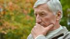 Ein Senior in Denkpose.