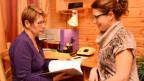 Zwei Frauen bei einem Bewerbungsgespräch. Chefin sieht sich das Dossier der Bewerberin kritisch an.