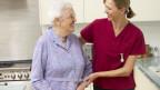 Jüngere Frau hilft Seniorin in der Küche.