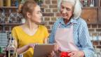 Seniorin und junge Frau beim Kochen mit Tablet in der Hand.