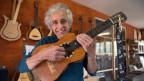 Daniel Meier hält eine Gitarre in der Hand.
