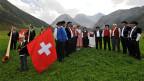 Jodler und Alphornspieler stehen auf einer Alpwiese bei Davos.