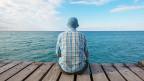 Ein Mann sitzt auf einem Steg am Wasser.