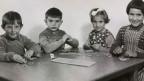 Zwei Buben und zwei Mädchen an einem Schulpult.