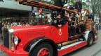 Feuerwehrleute sitzen in einem alten Löschfahrzeug.