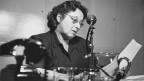 Eine Frau mit Brille vor einem Mikrofon.