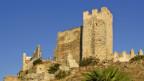 Eine Burgruine steht auf einem Hügel.