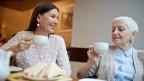 Zwei Frauen trinken zusammen Kaffee.