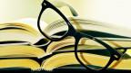 Eine Brille liegt auf Büchern.
