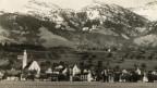 Altes Foto eines Dorfes vor Bergkulisse.