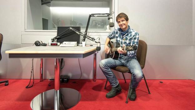il gitarrist Paul Etterlin cun sia gitarra