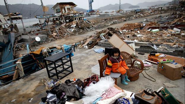 Ein Mädchen mit dem wenigen Hab und Gut, das der Tsunami seiner Familie gelassen hat.