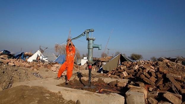 Ein kleiner Junge spielt mit einer Handpumpe. Im Hintergrund die durch die Fluten zerstörten Häuser seiner Familie. Auch Monate nach der Flutkatastrophe sind die Flutopfer auf Hilfe angewiesen.
